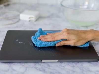 wiping down the exterior of a laptop