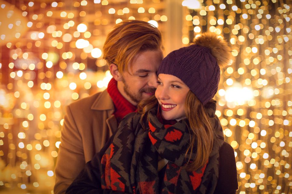 couple snuggling surrounded by twinkle lights.