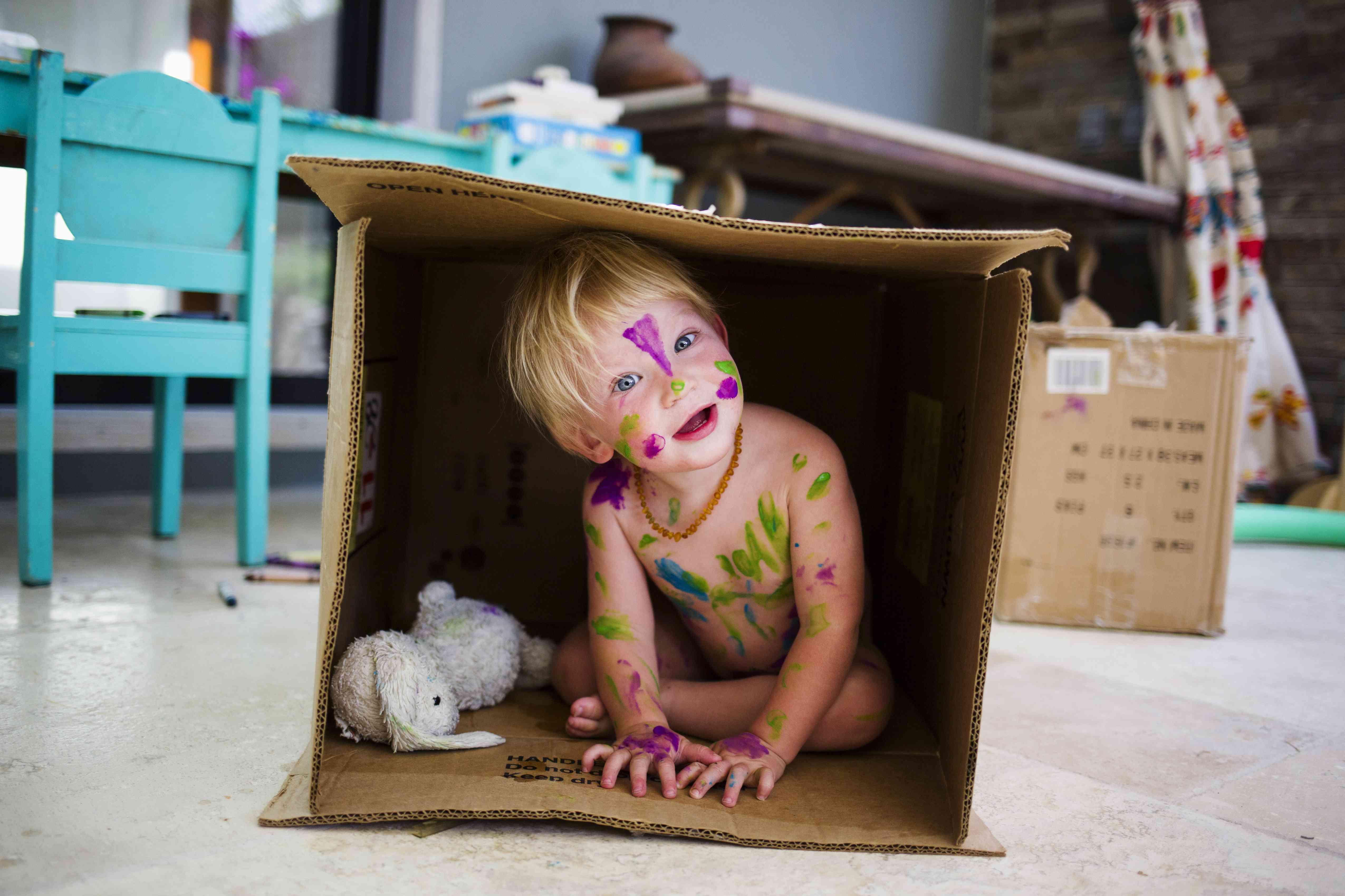 Naked baby boy wearing body paint in cardboard box on floor