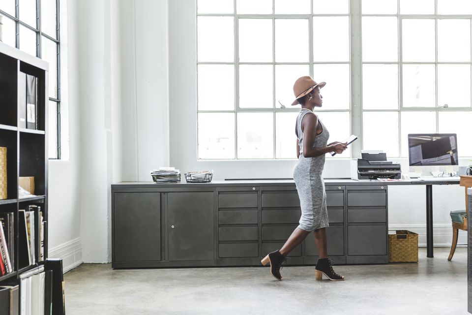 Full length side view of fashionable businesswoman holding digital tablet while walking at creative workplace