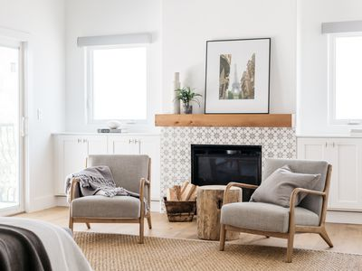 Light-filled living room with a decorated fireplace behind two chairs and firewood