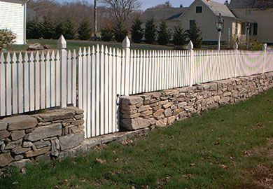Picture of a picket fence on a wall. The picket fence is capped with finials.