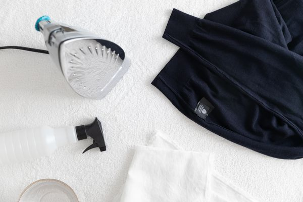 A wool sweater with an iron and other cleaning materials