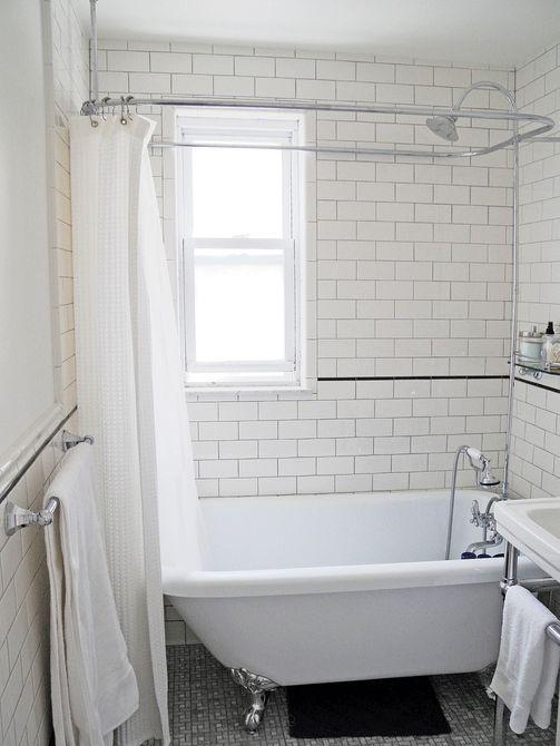 Azulejos blancos del metro y bañera con patas en el baño remodelado