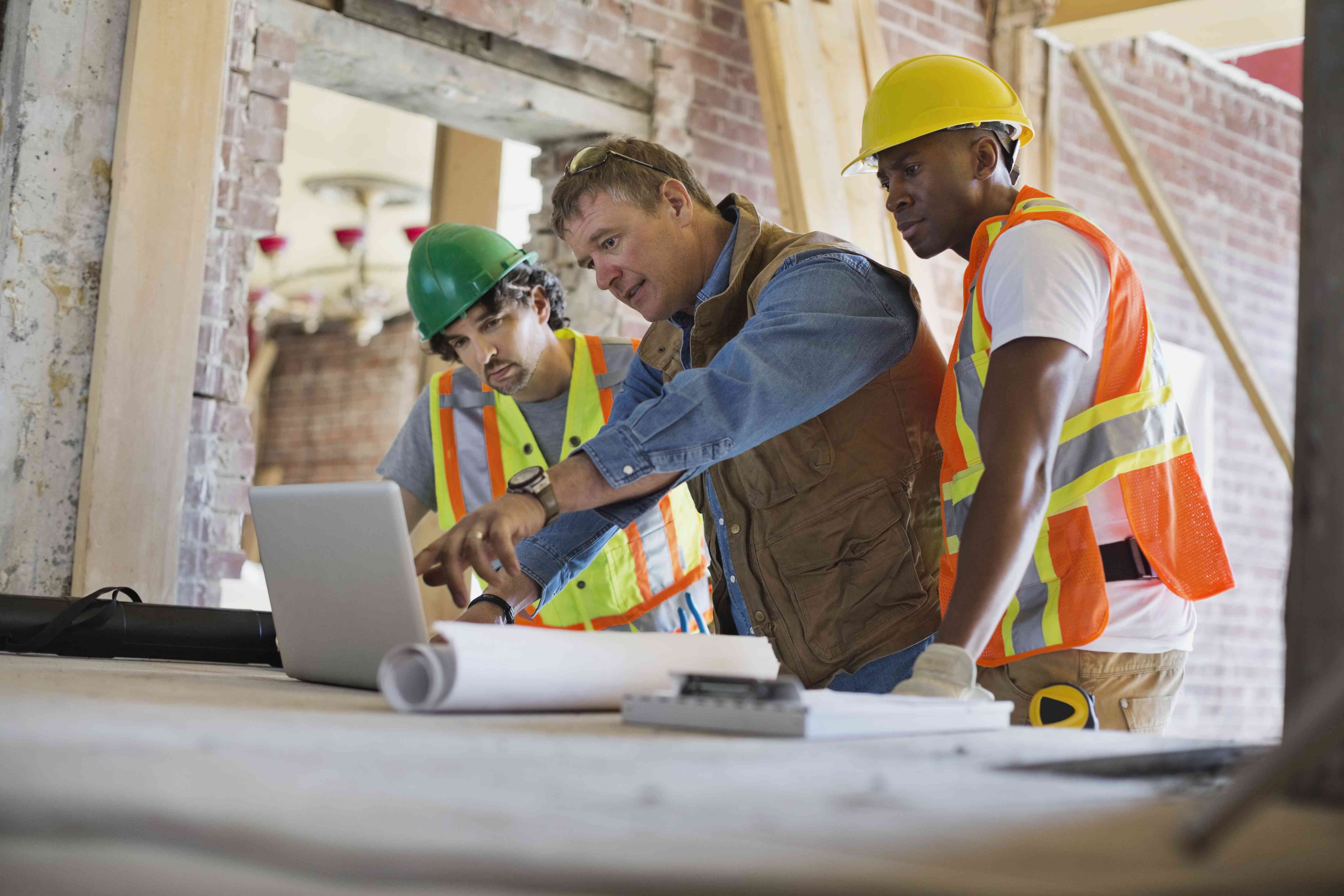 Foreman discussing plan on laptop with tradesmen at construction site