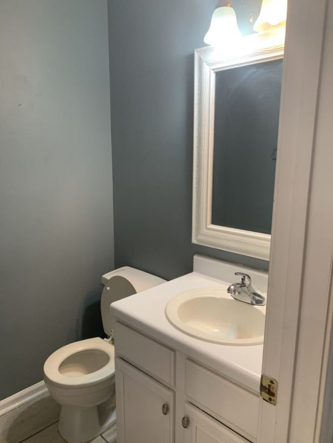 Small bathroom with blue-gray walls and no art.