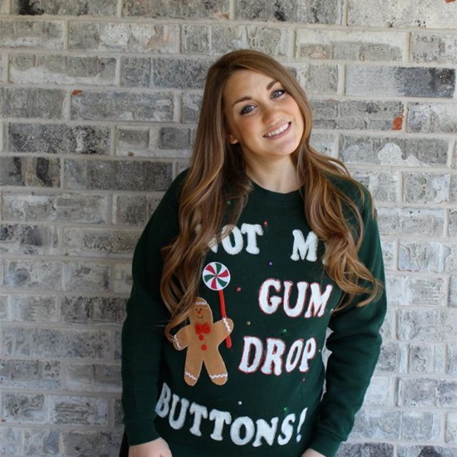 A woman wearing a green Christmas sweater