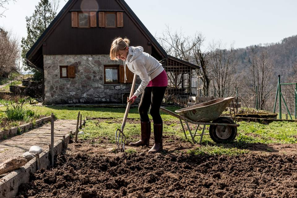 Woman Digging Dirt In Mountain Garden
