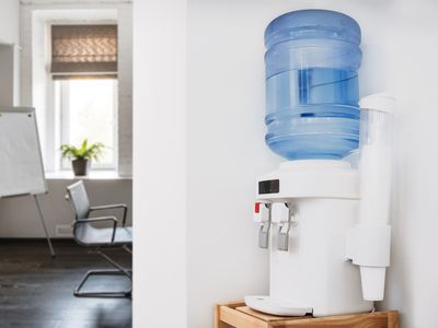 Water dispenser in corner of room with large blue plastic container on top
