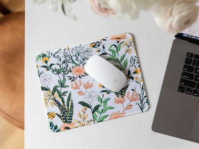 Mousepad with florals and foliage design under white mouse next to laptop