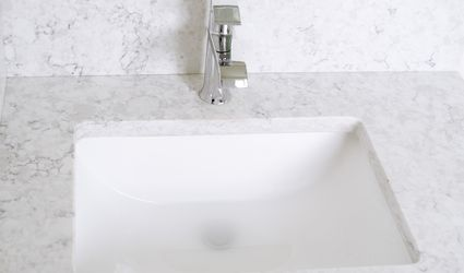 Water in a slow draining sink surrounded by white marble