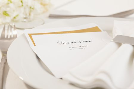 Close Up Of Wedding Invitation On Plate