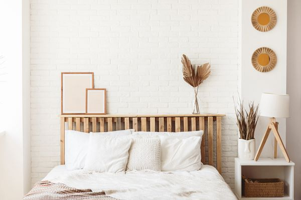 Wooden headboard with dry gold palm leaves in a glass vase and two photo frames on it.