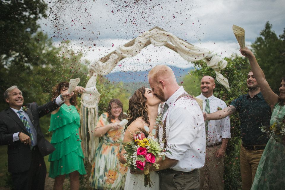 Newly married couple kissing after their outdoor wedding ceremony while guests throw flower petals