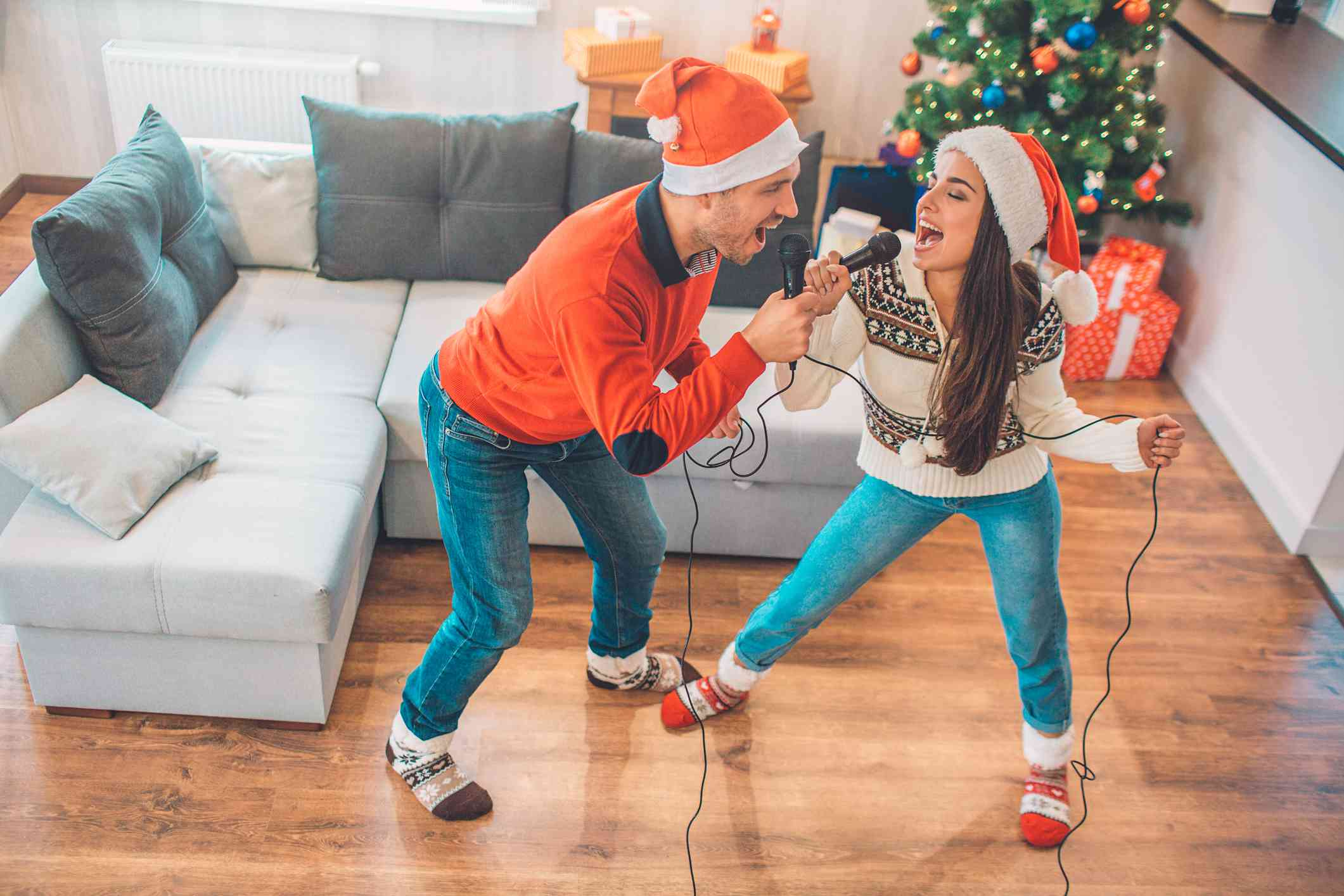 Emotional couple standing and singing together using microphone. They look at each other. People singing out loud. They wear Christmas clothes.