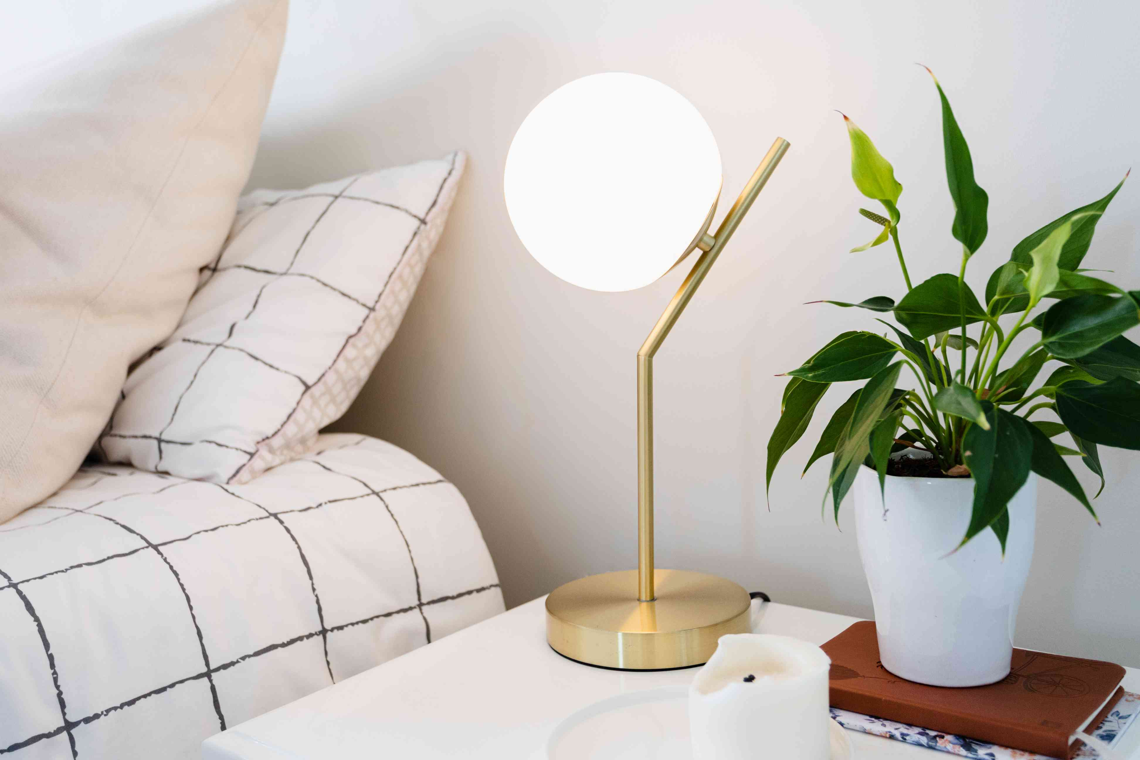 Lighted gold lamp with orb next to potted plant and bed