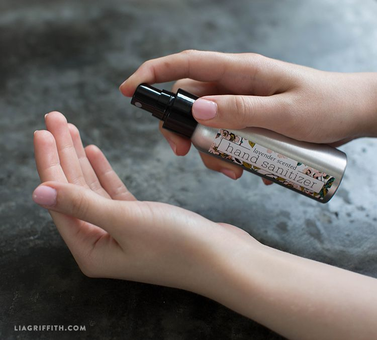 A woman spraying her hands with hand sanitizer spray