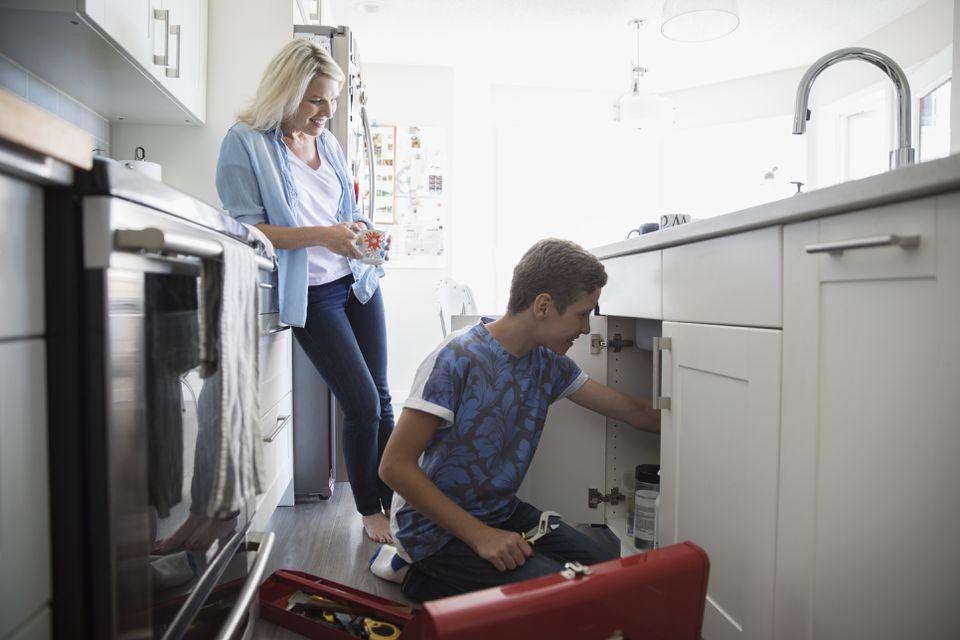 mother watching pre-adolescent son install under kitchen sink