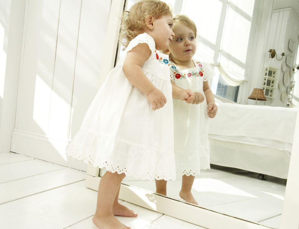 a child looking in a mirror in a room decorated in all white