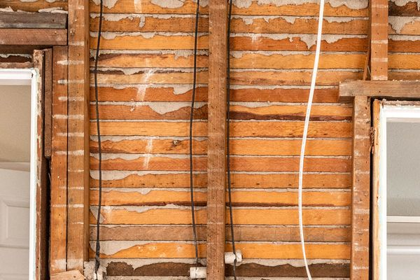 Lath and plaster walls exposed in home renovation with wires hanging