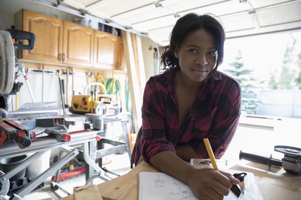 A woman drawing sketches in her garage