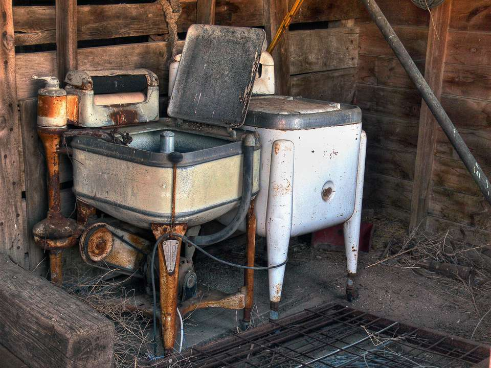 Two old antique wringer washing machines sit rusting away in an abandoned barn on the plains of South Dakota
