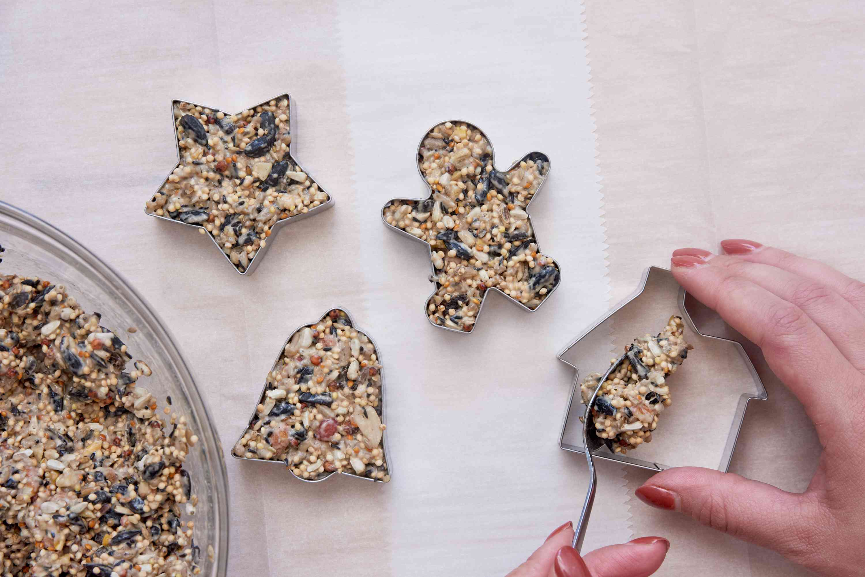 filling cookie cutters with birdseed mixture