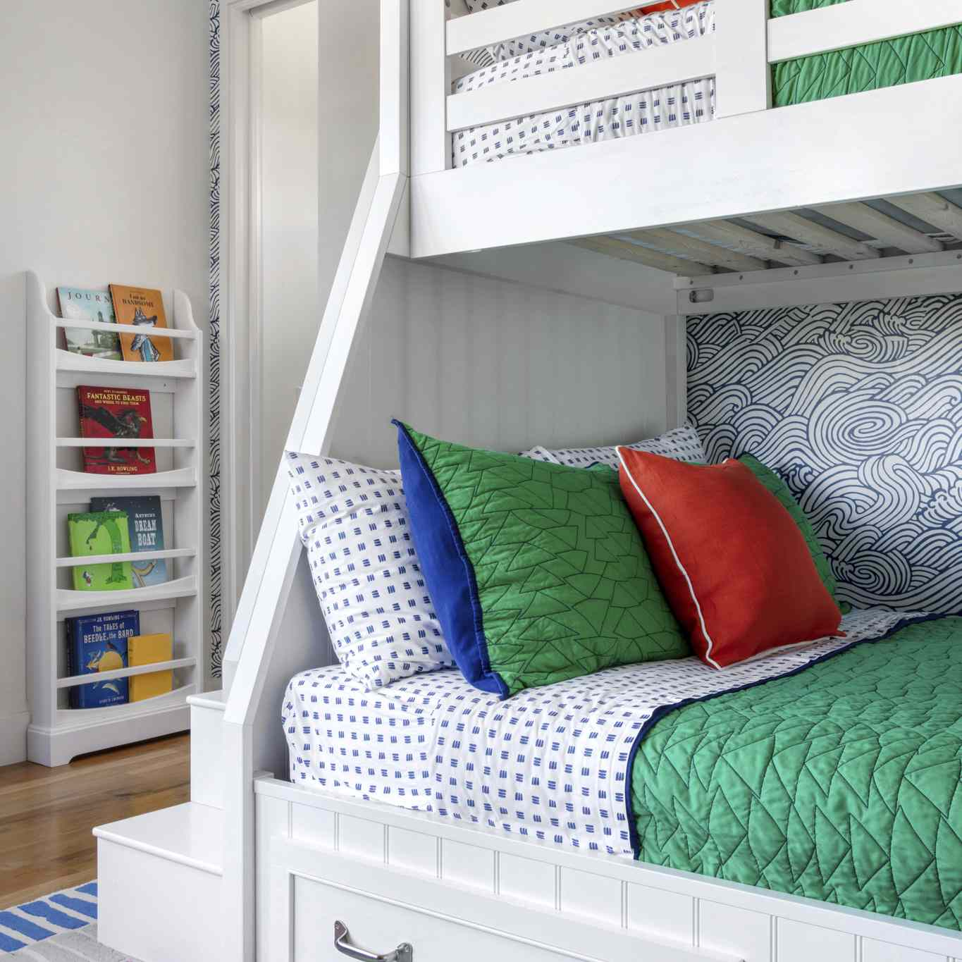 swirly blue-and-white wallpaper in this kid bedroom featuring a bunk bed and primary colors