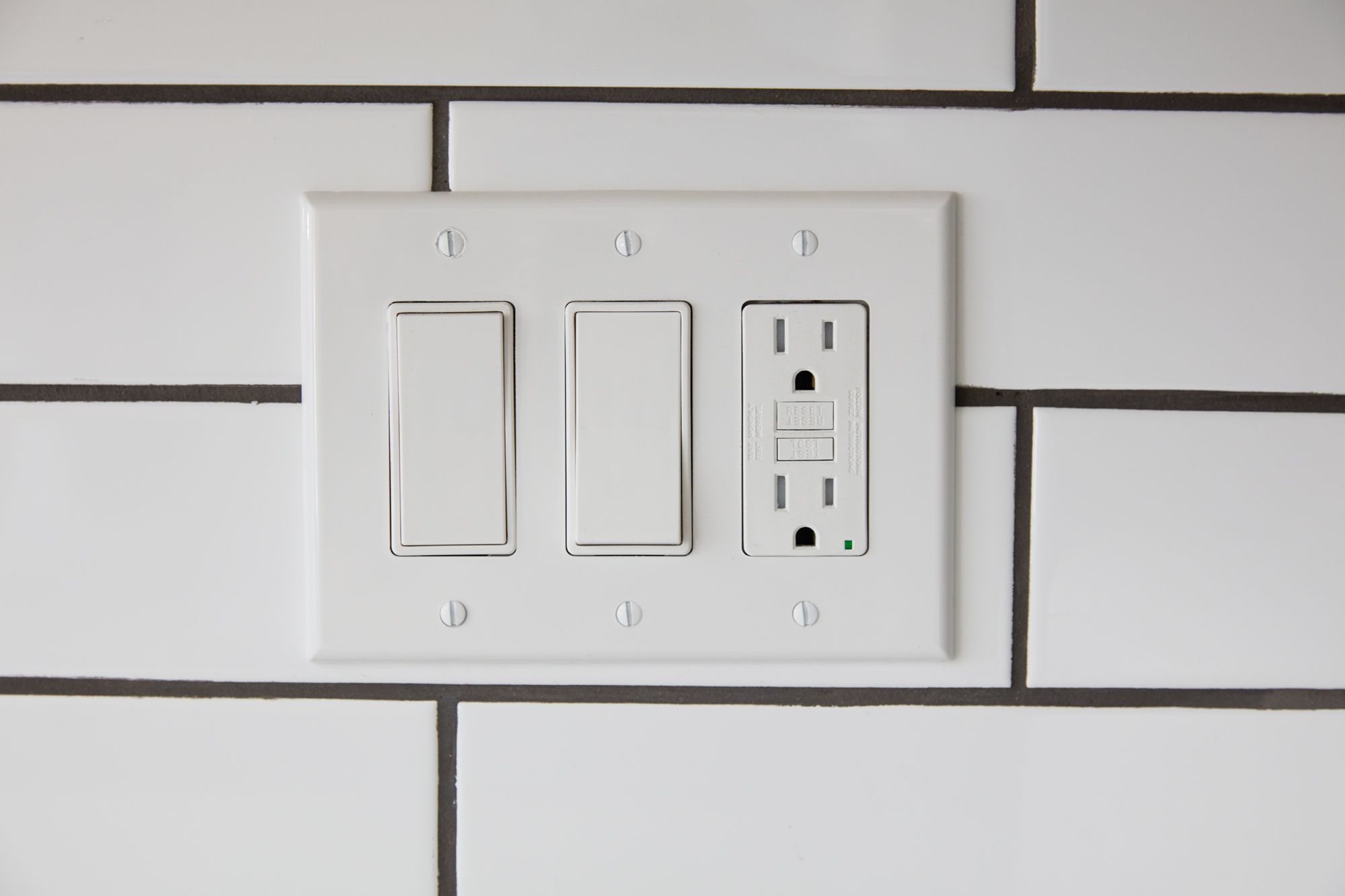 Kitchen outlet with two white switches on tiled wall