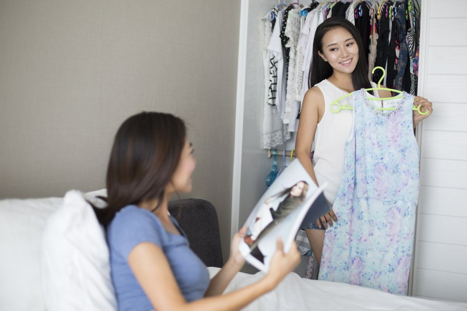 Young girl choosing dress from closet