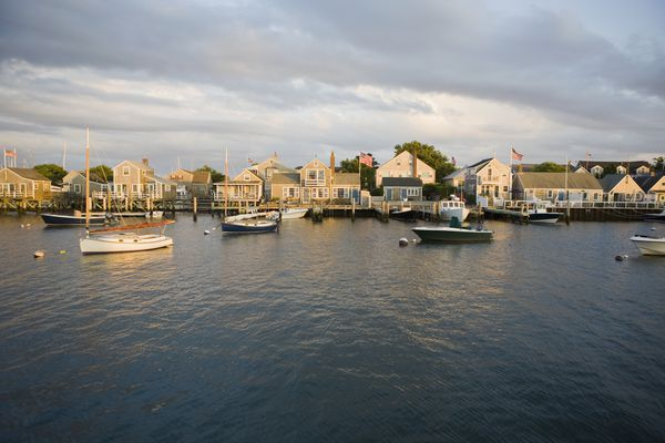 Boats in harbor with village in background
