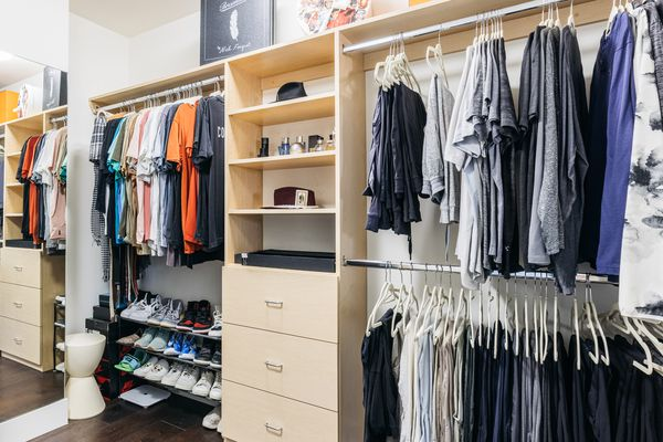 Walk-in closet with clothes hanging and shoes organized near cabinet drawers