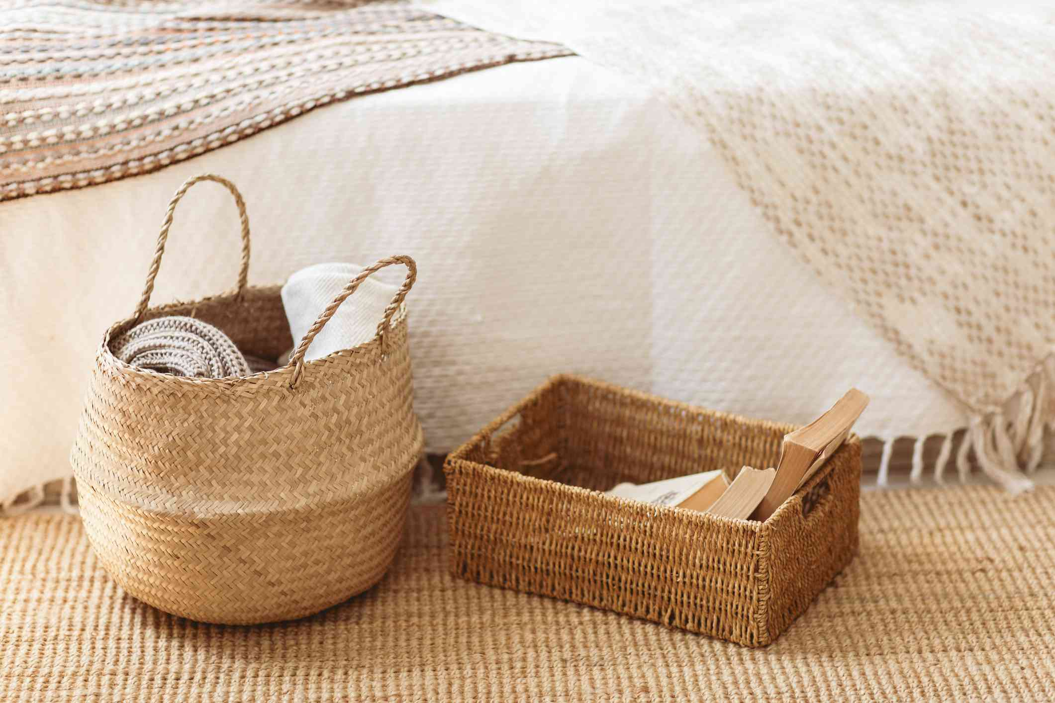 A blanket basket and basket of books next to a bed