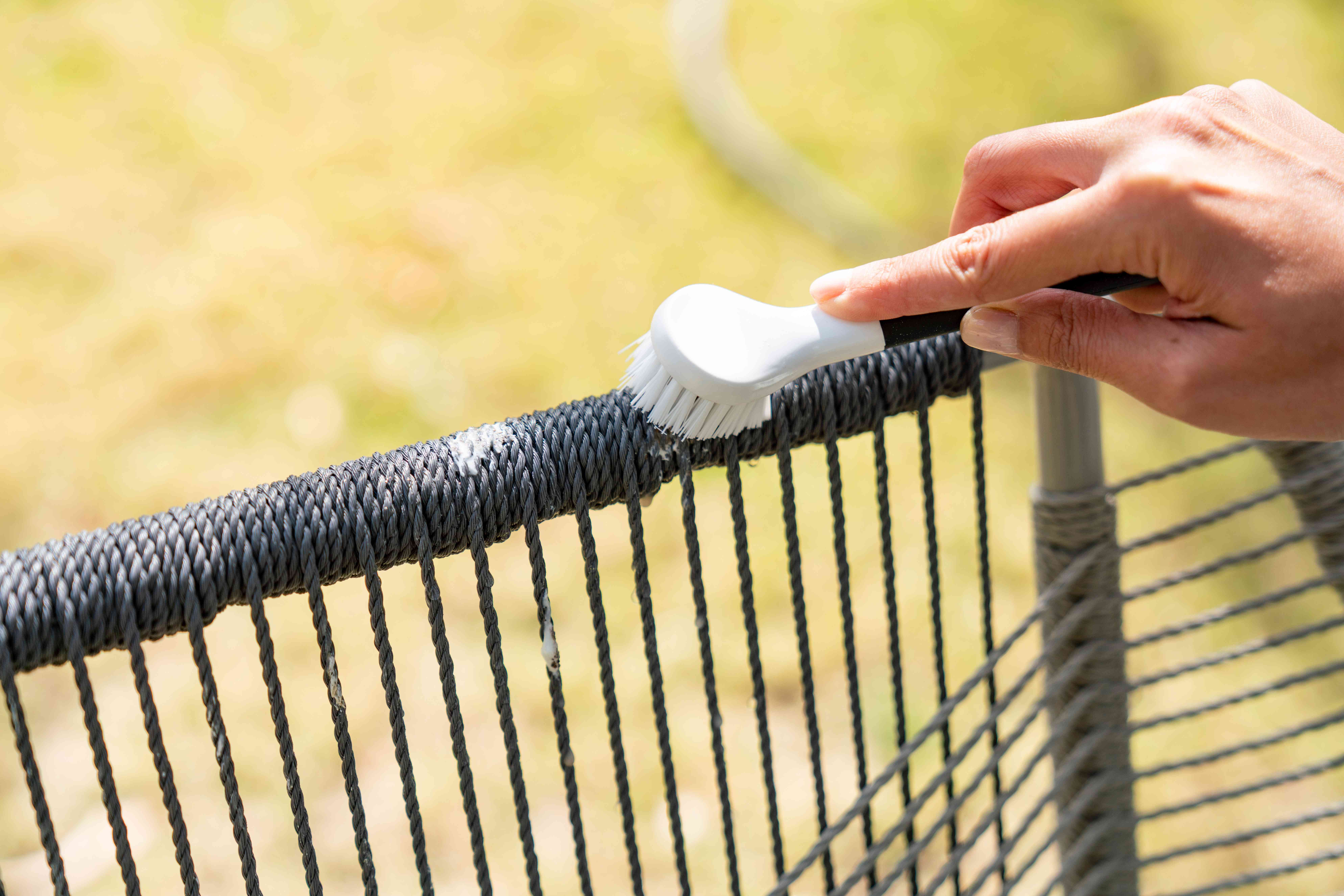 Soft-bristled brush scrubbing away bird poop on outdoor fabric