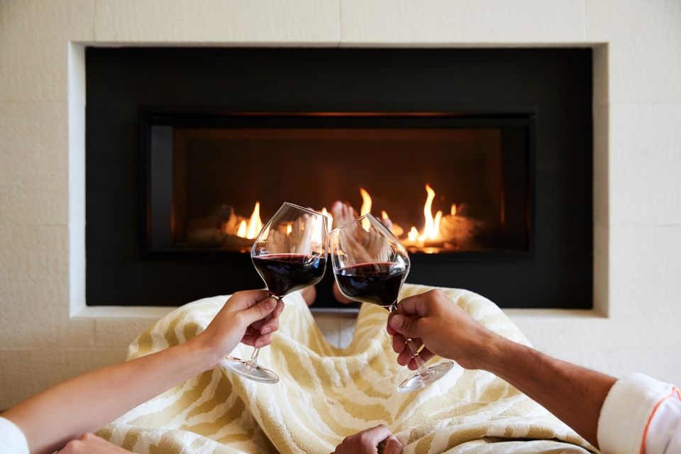 a couple toasting wine by the fire