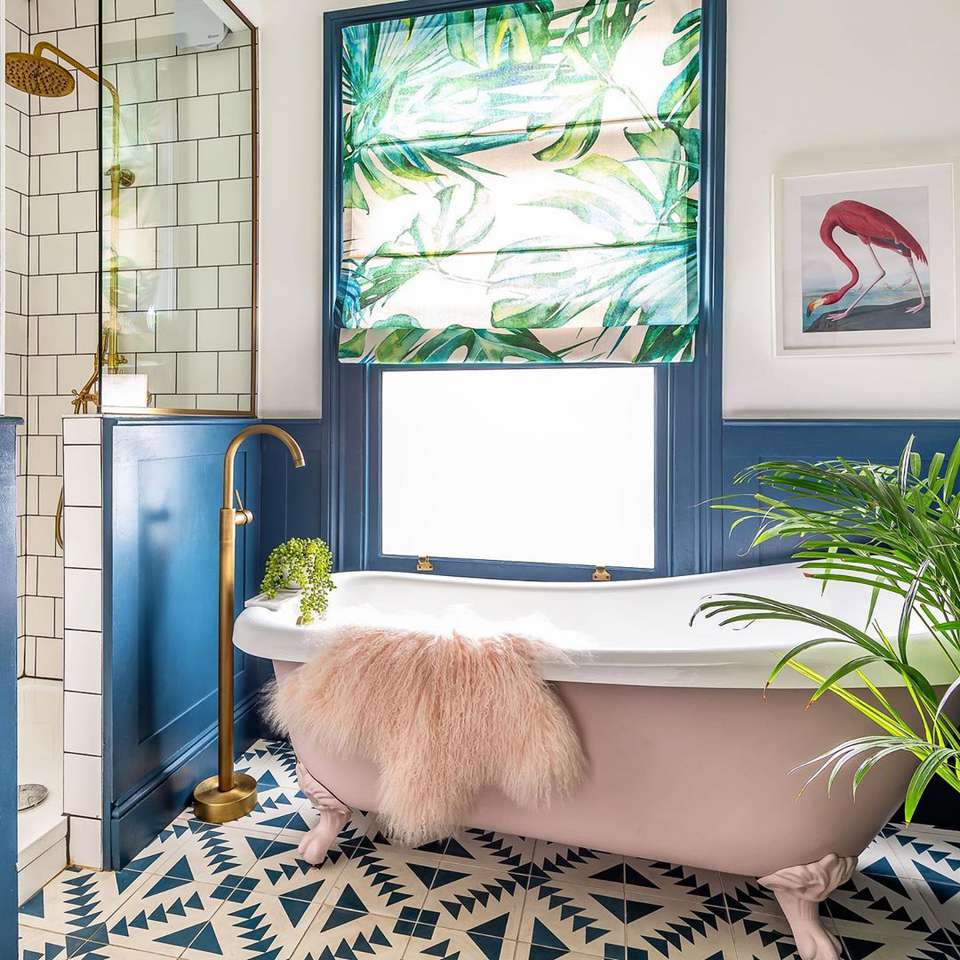 Bathroom with designed flooring and pink bathtub