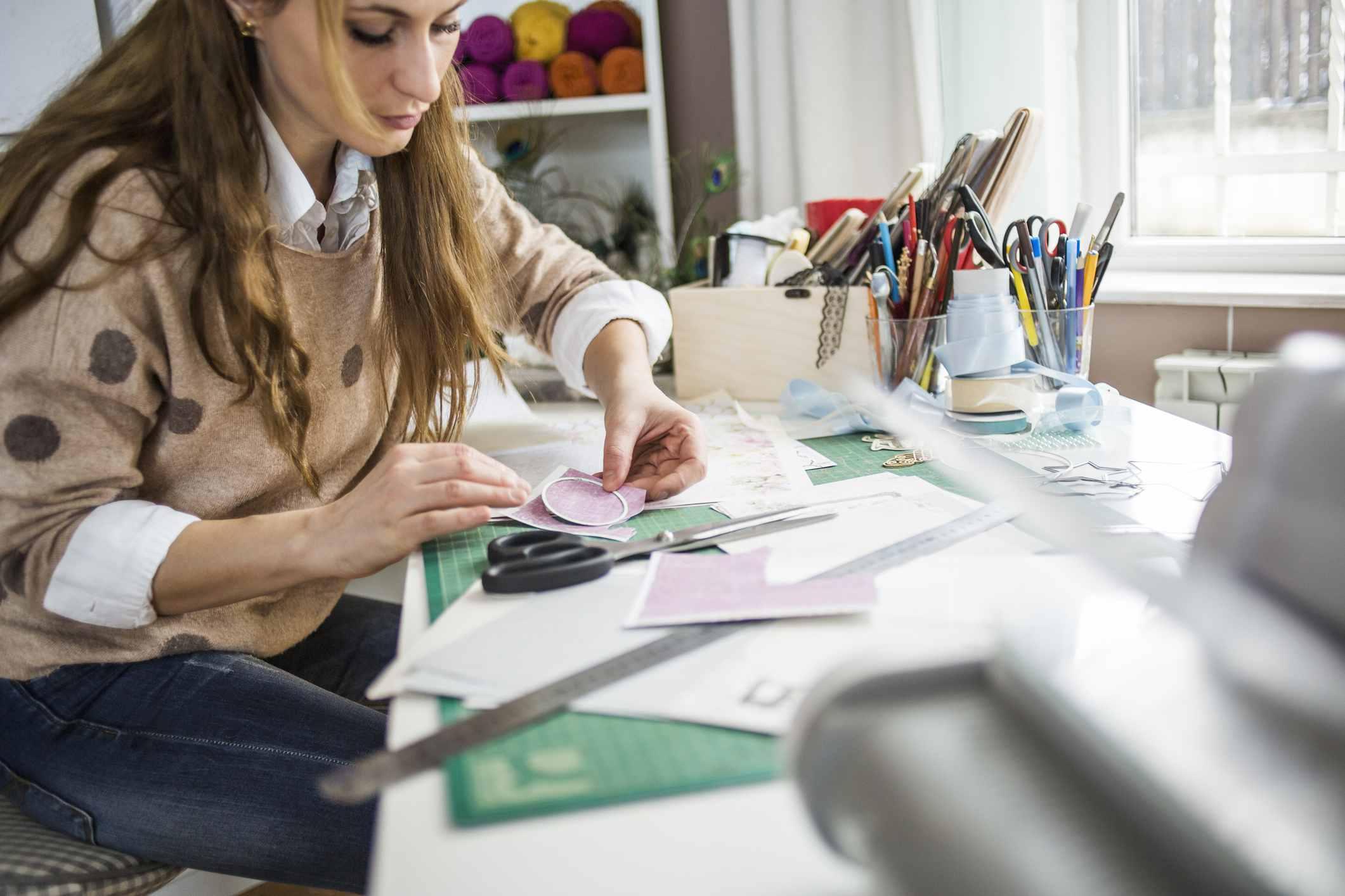 Mujer trabajando con papel en una mesa de manualidades