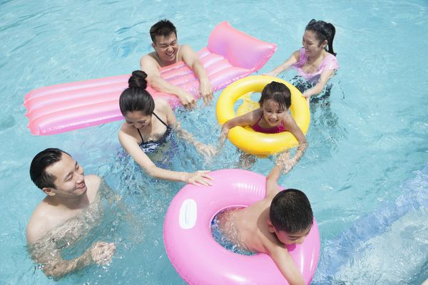 Asian family playing with inflatable pool toys
