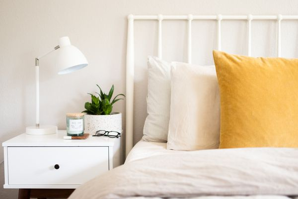White nightstand with white night lamp and decor items next to bed with pillows and white headboard closeup