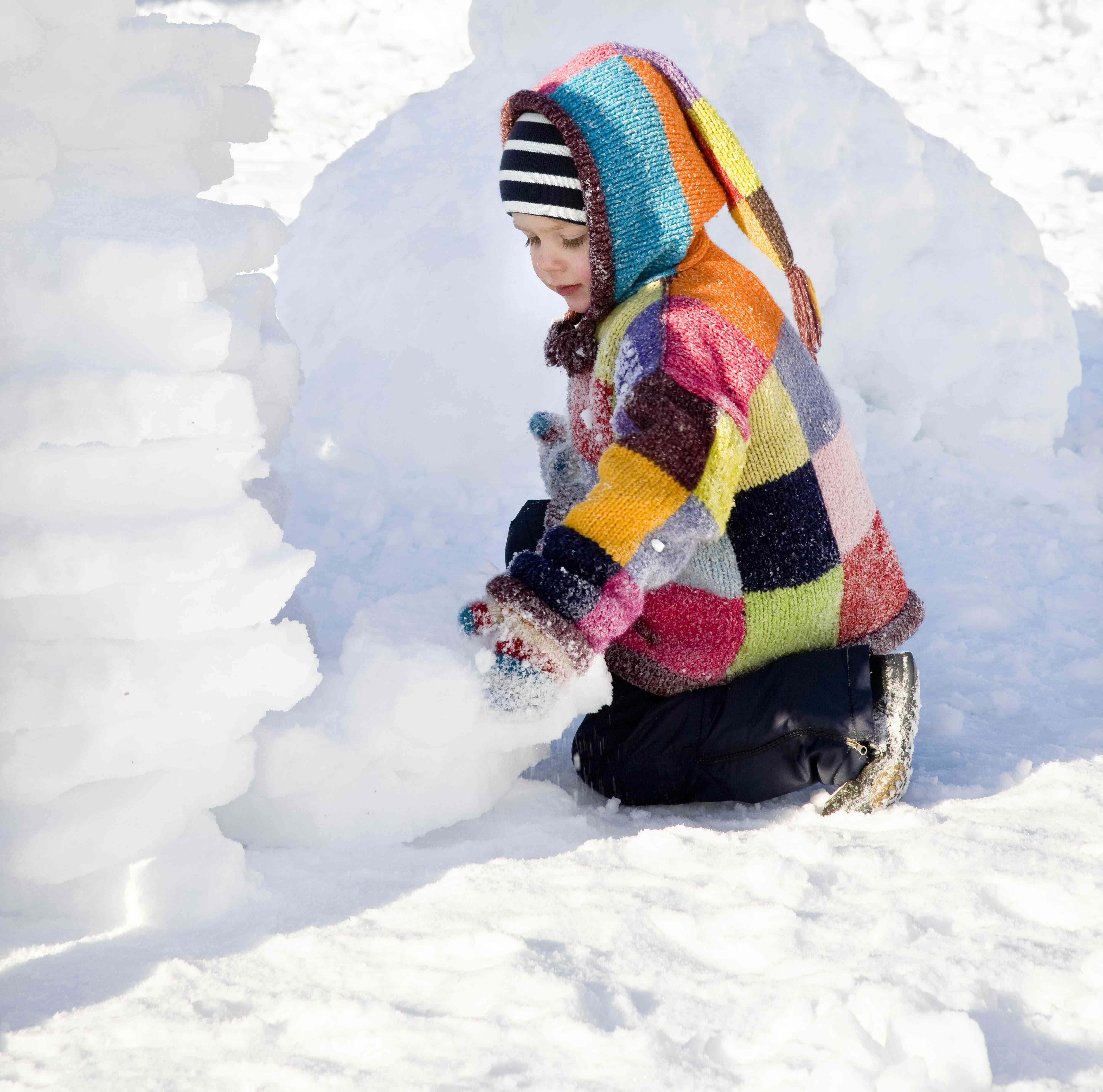 boy building igloo in the snow