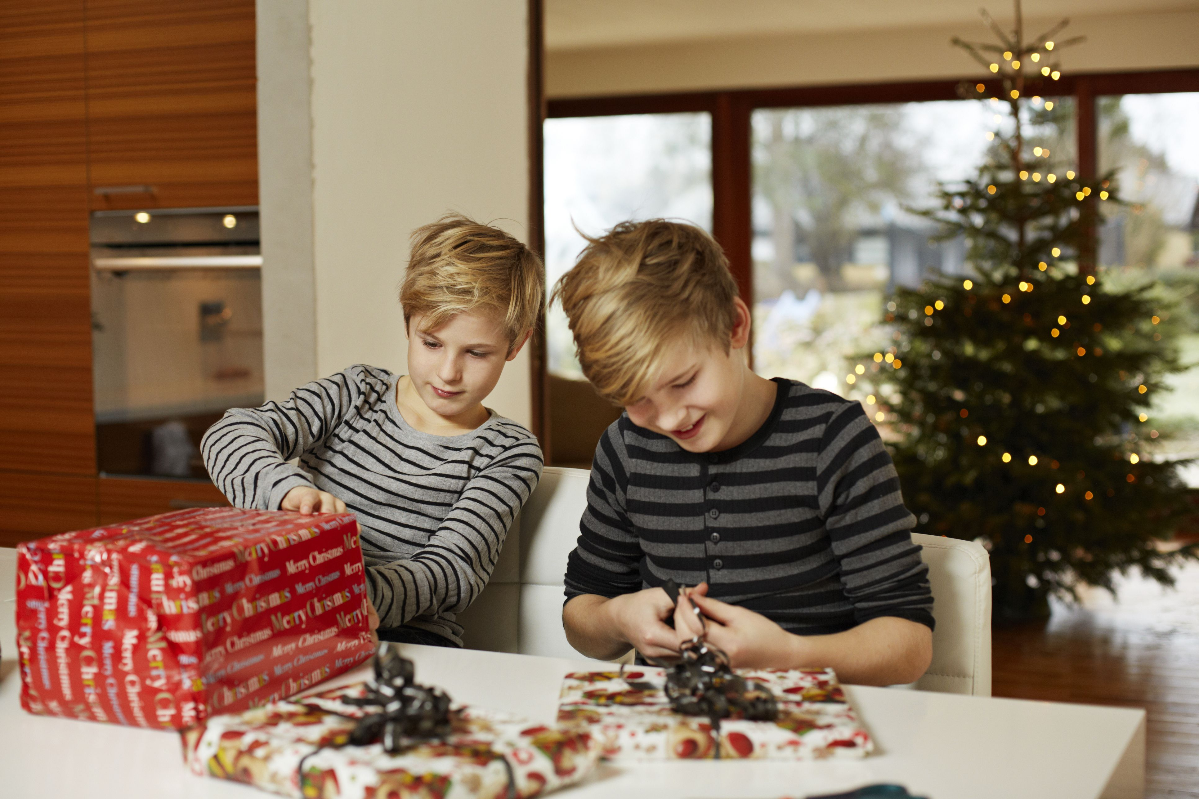 Brothers wrapping up presents for christmas