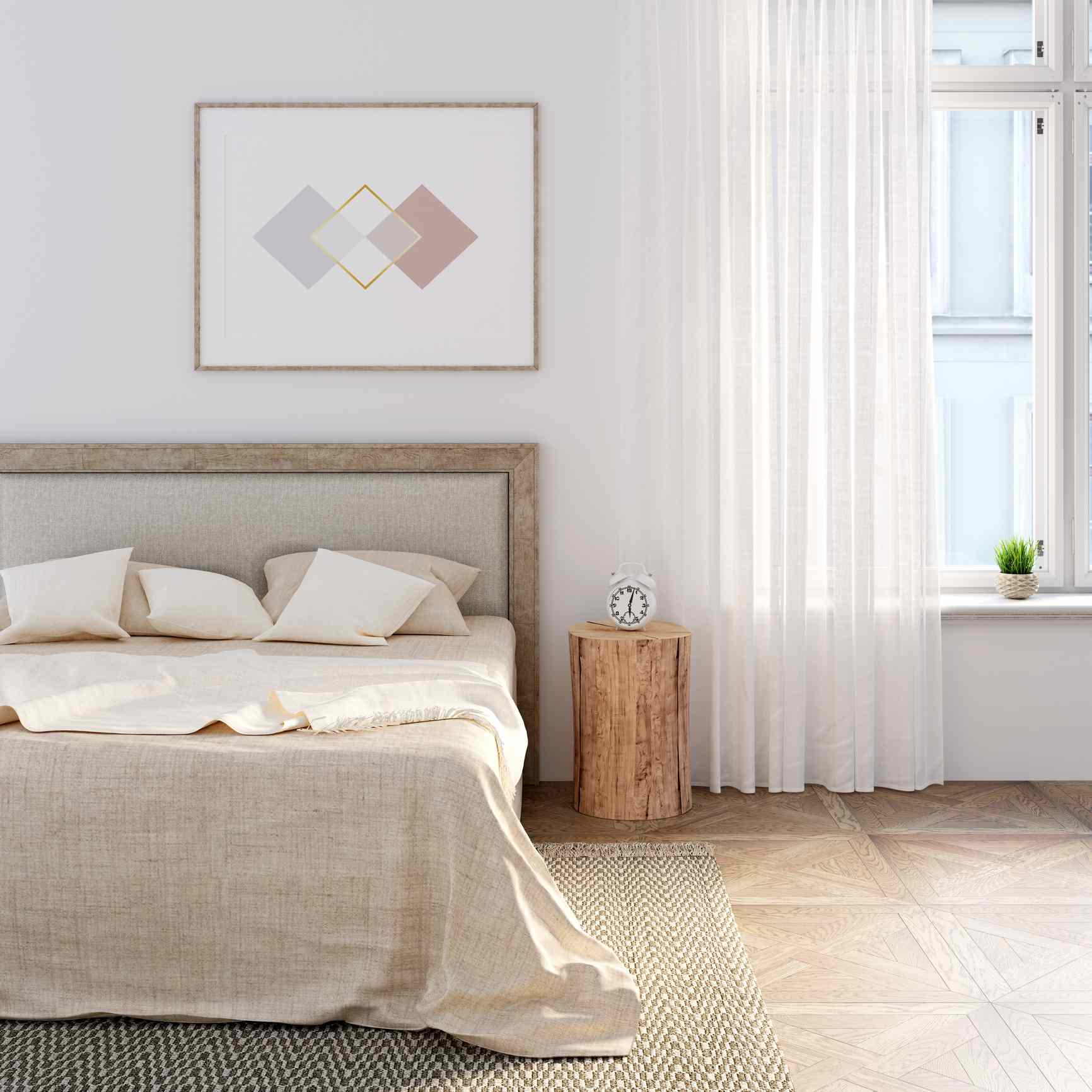 White bedroom with natural linen on the bed, the horizontal poster above the headboard. An alarm clock stands on a stump between a bed and a window with a linen curtain