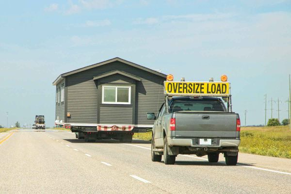 a mobile home on a trailer on the highway