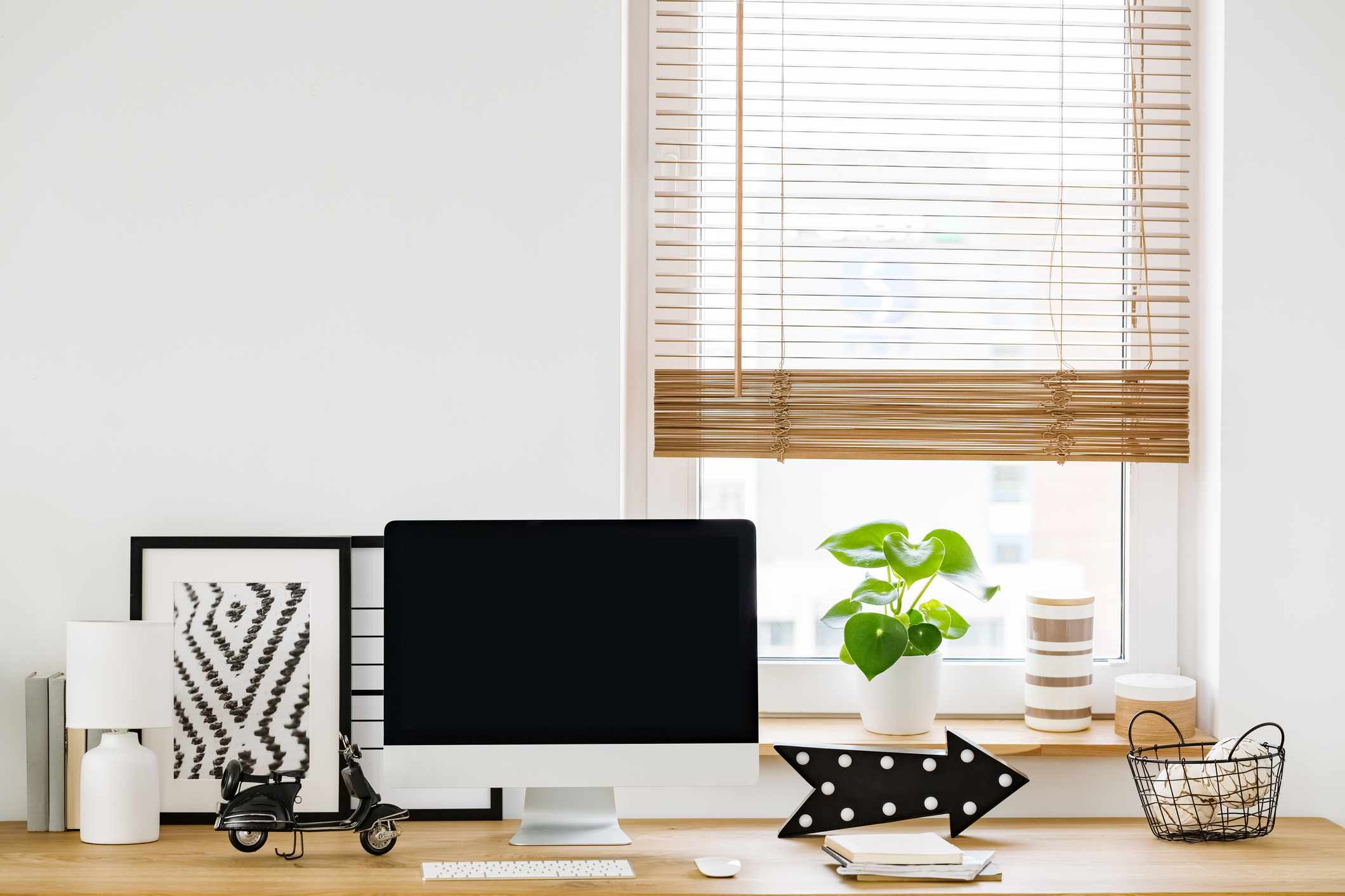 Close-up on a minimalist, white workspace interior by a window with a modern computer and simple decorations on a wooden desk