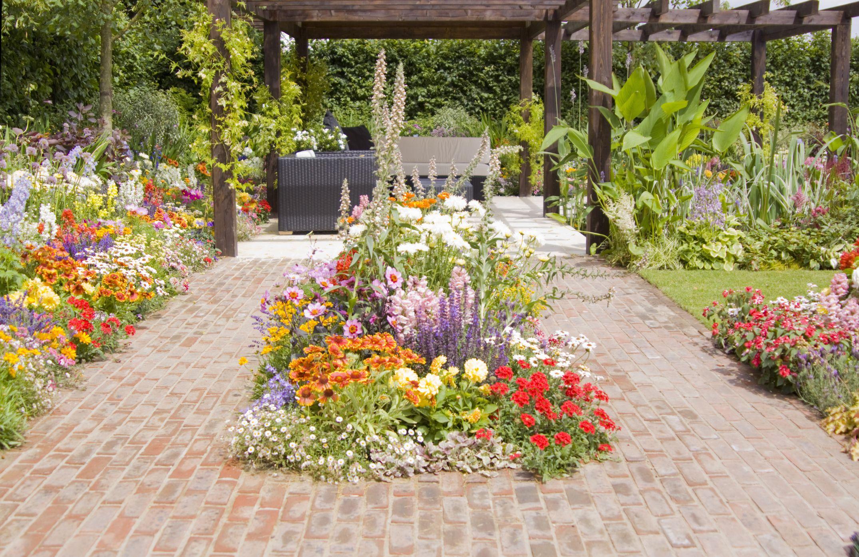 Patio de ladrillo con flores y pérgola