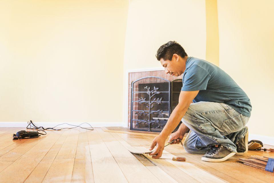 A tradesman installing a wood floor