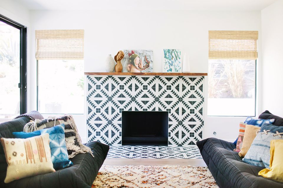 Cement tile fireplace in living room with two couches.