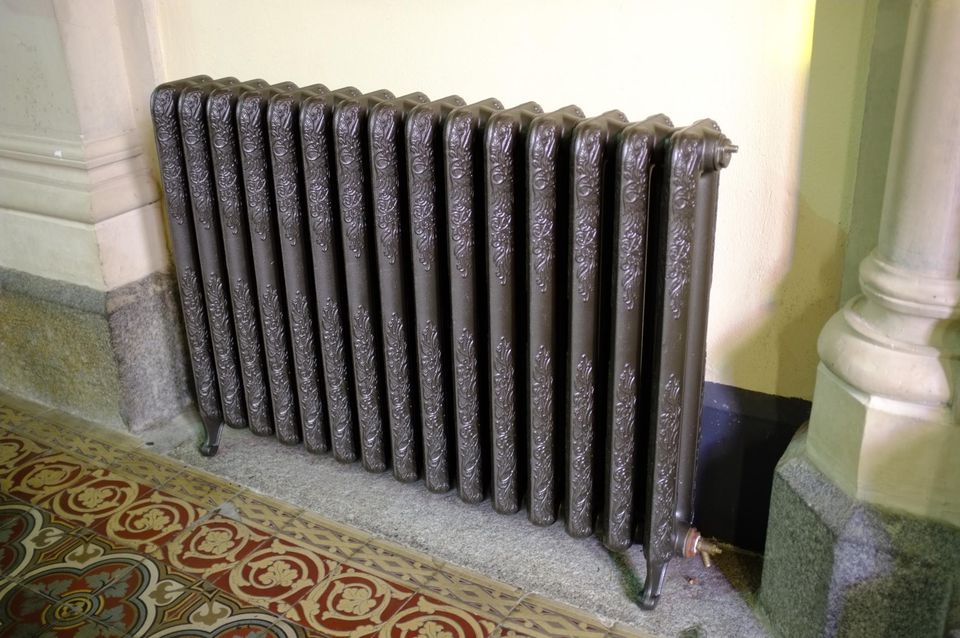 Wide angle image of cast iron radiator.