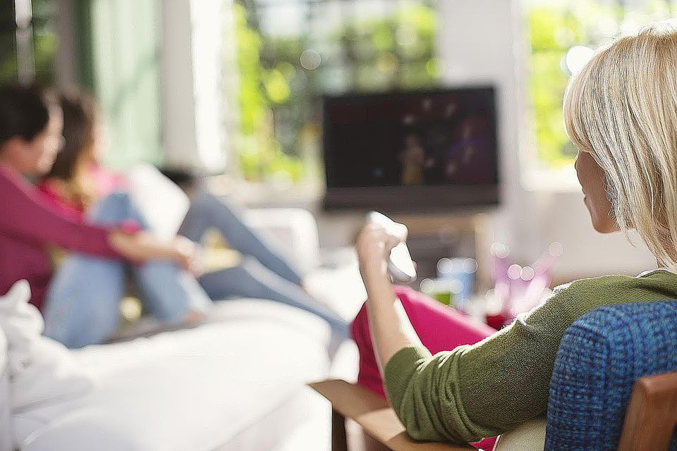 Woman switching channel on television