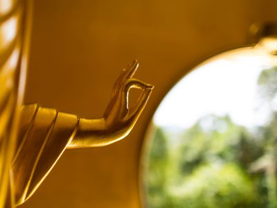 golden buddha statue with window in background